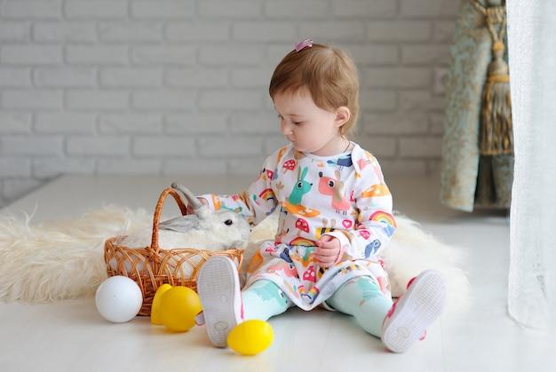 Petite fille avec panier de pâques et lapin de pâques