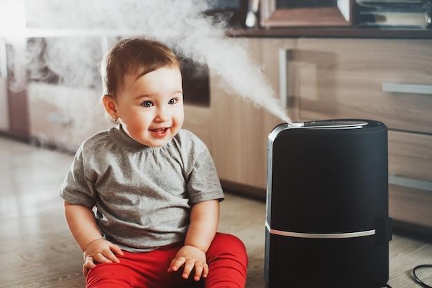 Une petite fille en pantalon rouge est assise à côté d'un humidificateur