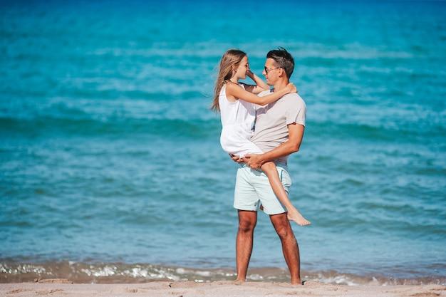 Petite fille et papa heureux s'amusant pendant les vacances à la plage