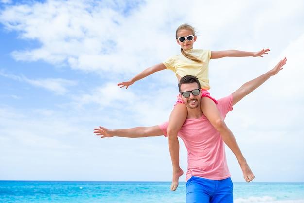 Petite fille et papa heureux s'amuser pendant les vacances à la plage