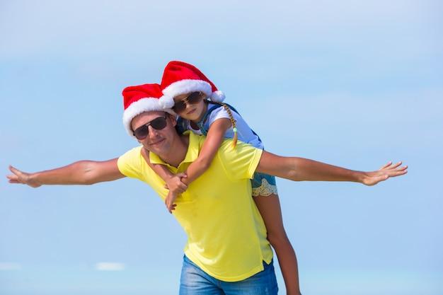 Petite fille et papa heureux à santa hat pendant les vacances à la plage