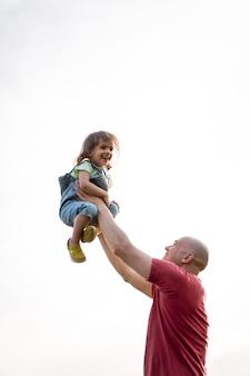 Petite fille avec papa papa jette bébé en l'air. rire joyeux, enfant émotif, bonheur.