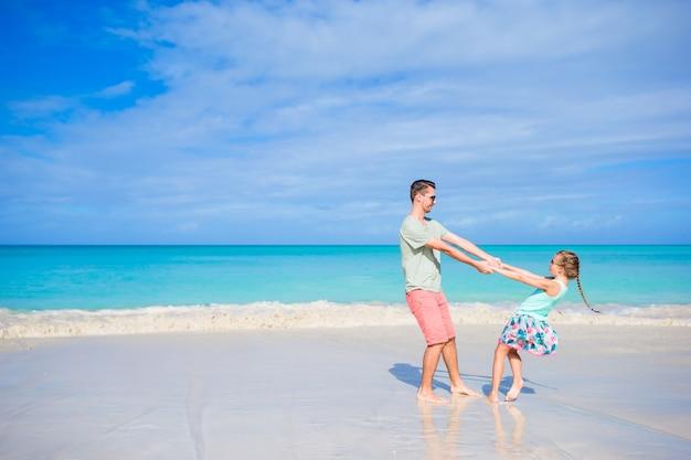 Petite fille et papa pendant des vacances à la plage tropicale