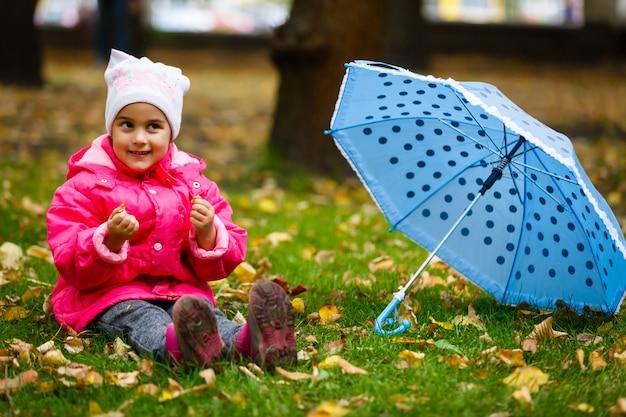 Petite fille avec un parapluie en plein air