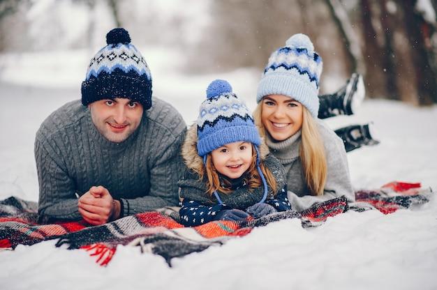 Petite fille avec des parents assis sur une couverture dans un parc d'hiver