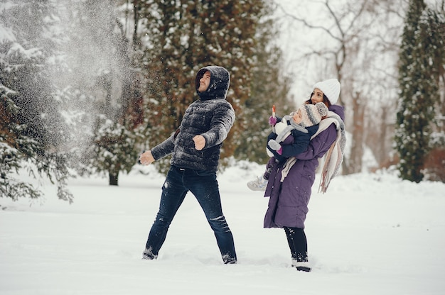 Petite fille avec des parents dans un parc d'hiver