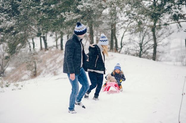 Petite fille avec des parents jouant dans un parc d'hiver