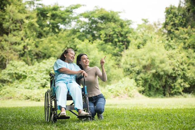 Petite-fille parle avec sa grand-mère assise sur un fauteuil roulant, concept joyeux, famille heureuse