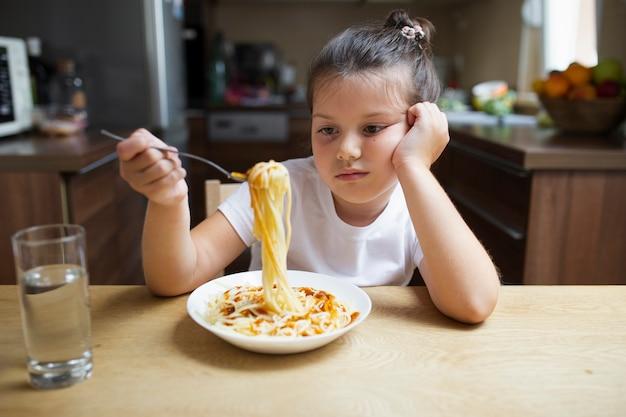 Petite fille pas heureuse avec plat de pâtes