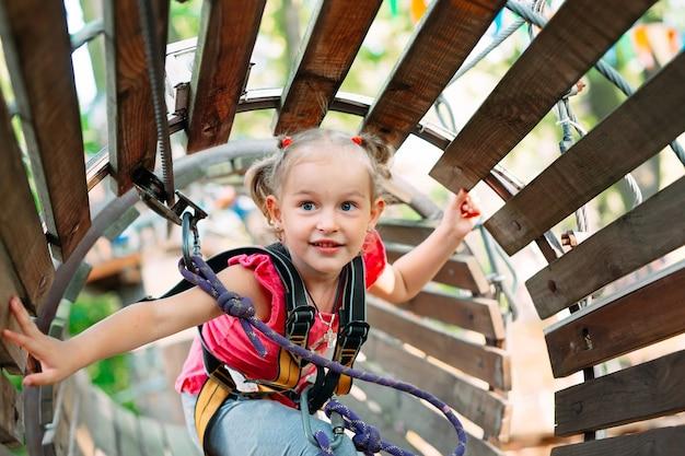 Une petite fille passe l'obstacle dans le parc de corde
