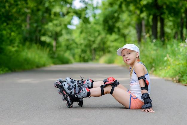 Petite fille en patins à roulettes dans un parc