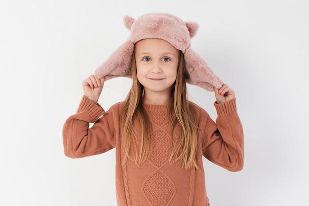 Petite fille payant avec son chapeau d'hiver