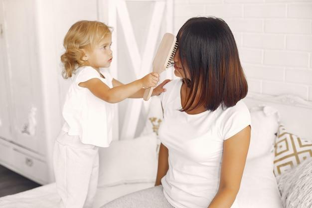 Petite fille peignant les cheveux de sa maman
