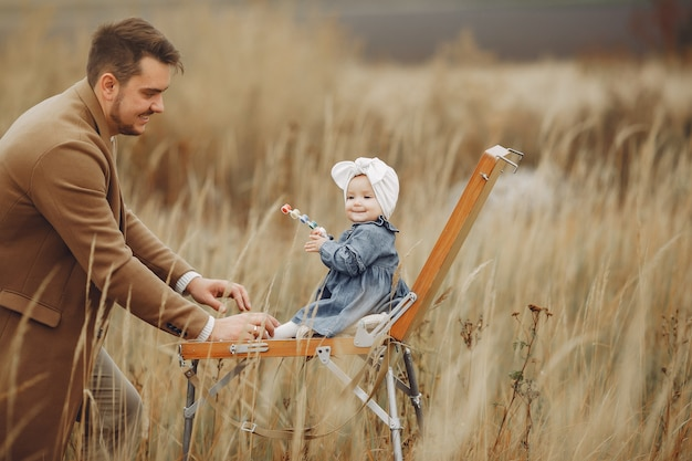 Petite fille peignant dans un champ d'automne avec le père