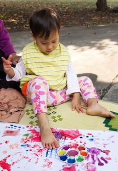 Petite fille peignant sur du papier blanc