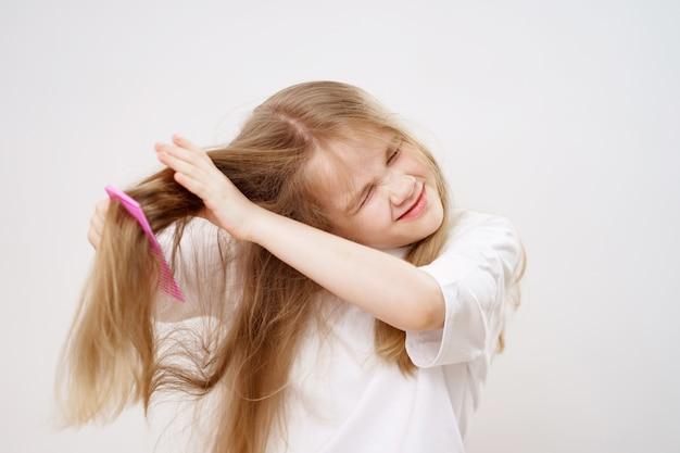 Petite fille peigne les cheveux emmêlés sur un fond blanc. cosmétiques pour le soin des cheveux des enfants.