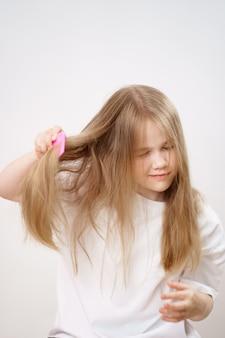 Petite fille peigne les cheveux longs et emmêlés sur un fond blanc. cosmétiques pour le soin des cheveux des enfants.