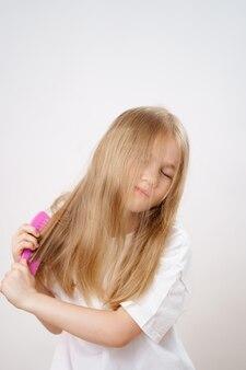 Petite fille peigne les cheveux longs et emmêlés sur fond blanc. cosmétiques pour le soin des cheveux des enfants.