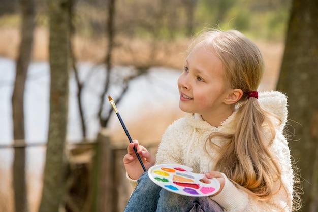 Petite fille peint au printemps sur la nature