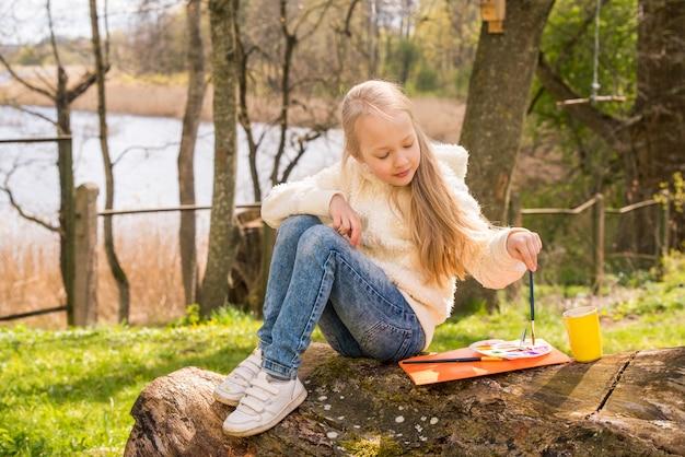 Petite fille peint une photo au printemps à l'extérieur sur la nature