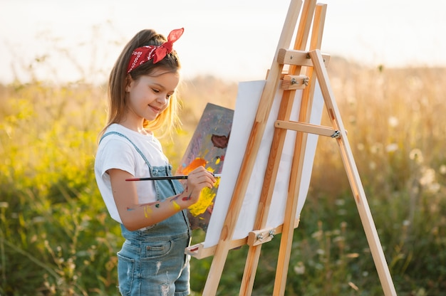 Petite fille peint une photo à l'extérieur