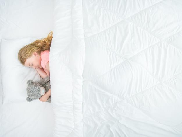 La petite fille avec une peluche dort sur le lit. vue d'en-haut