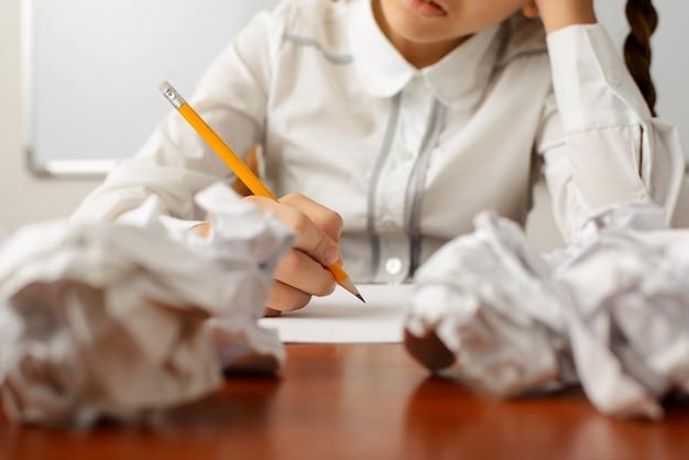 Petite fille pensant dur a échoué plusieurs fois en écrivant une composition sur le sujet difficile