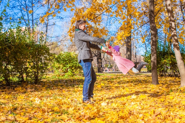 Petite fille avec un père heureux s'amuser dans le parc automne par une journée ensoleillée