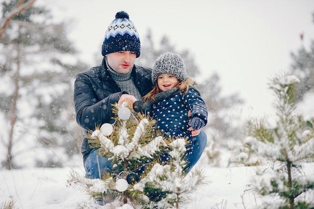 Petite fille avec père jouant dans un parc d'hiver
