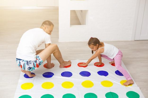 Petite fille et père jouent au twister à la maison