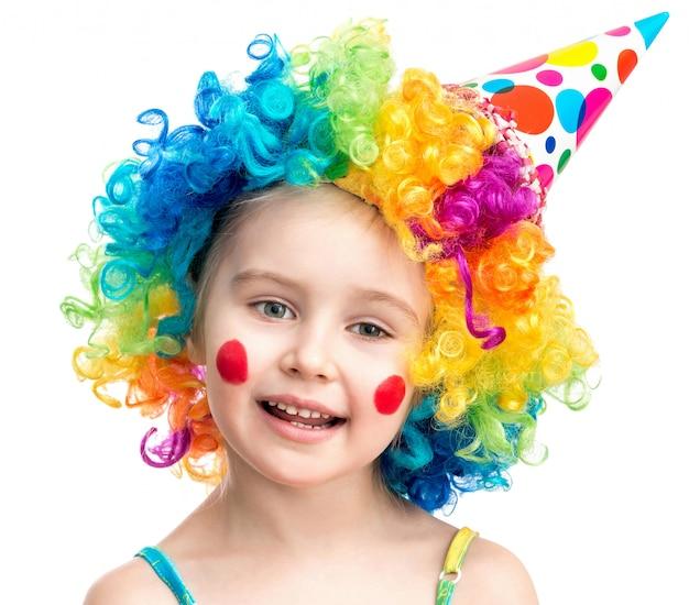Petite fille en perruque de clown isolé sur fond blanc