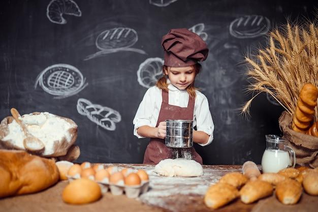 Petite fille, pétrir la pâte à table