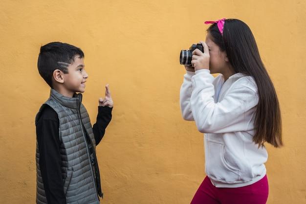 Une petite fille photographe prend une photo de son petit frère.
