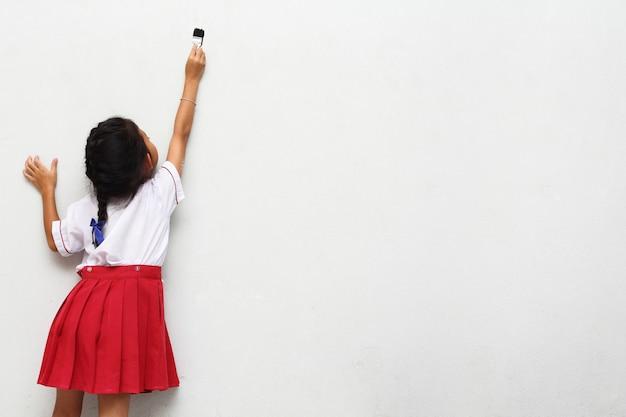 Petite fille, à, pinceau, sur, mur, vue postérieure