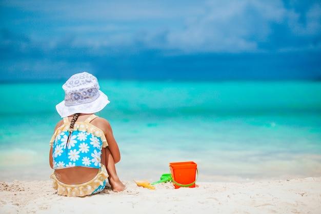 Petite fille à la plage blanche tropicale faisant le château de sable