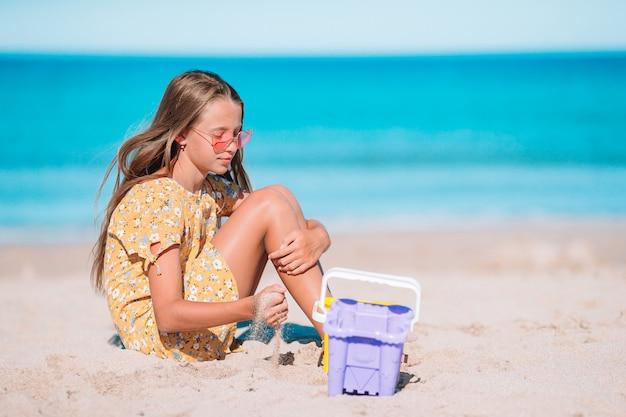 Petite fille sur la plage faisant un château de sable