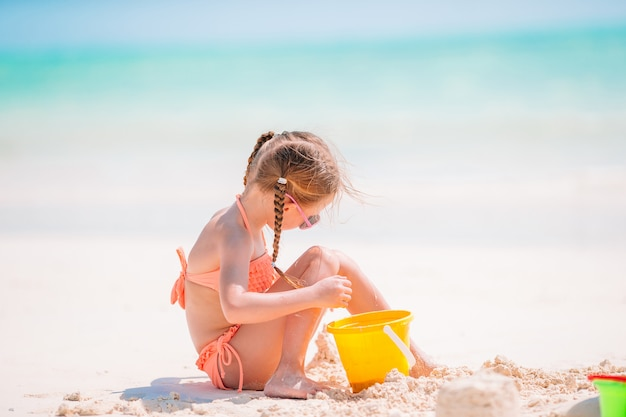 Petite fille, à, plage tropicale blanche, confection, château sable