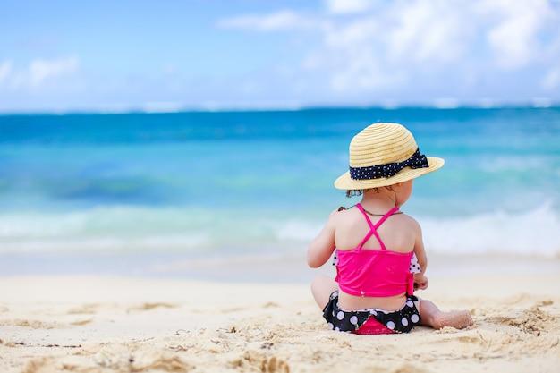 Petite fille à la plage tropicale blanche faisant château de sable