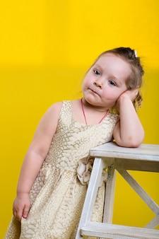 Petite fille avec planche en belle robe et lunettes sur fond jaune