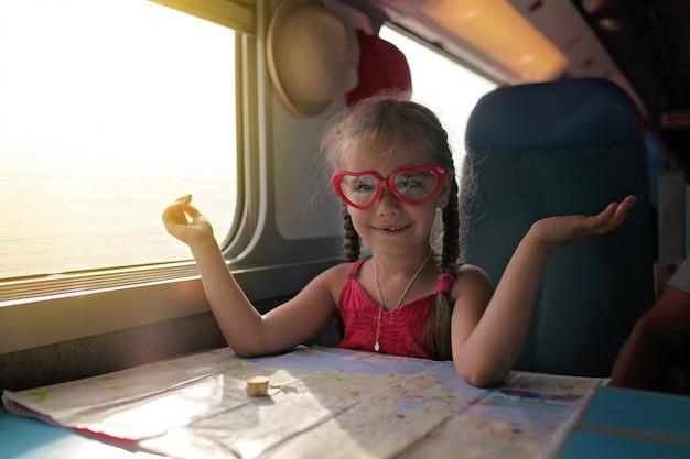 Petite fille avec la planification de ses vacances économiques lors d'un voyage en train