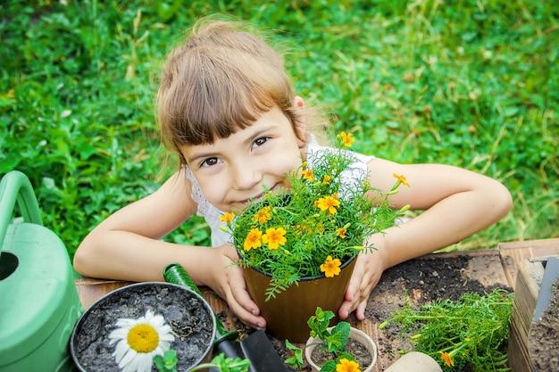 Une petite fille plante des fleurs. le jeune jardinier mise au point sélective.