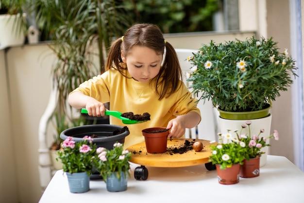 Petite fille planter des fleurs sur le balcon, prendre soin des plantes