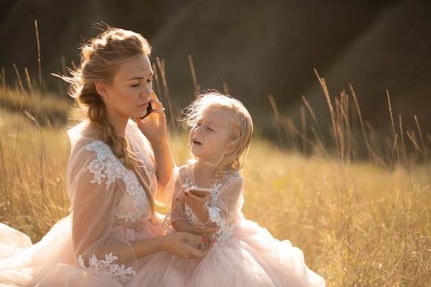 Une petite fille pleure pendant que sa mère parle au téléphone