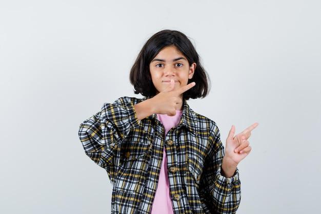 Petite fille pointant de côté en chemise, veste, vue de face.