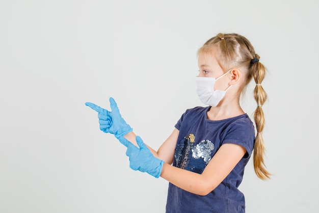 Petite fille pointant deux doigts à sideera en t-shirt, gants et masque.