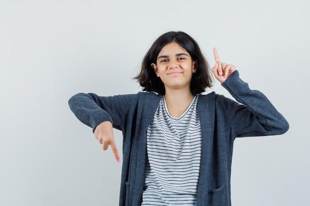Petite fille pointant les doigts de haut en bas en t-shirt