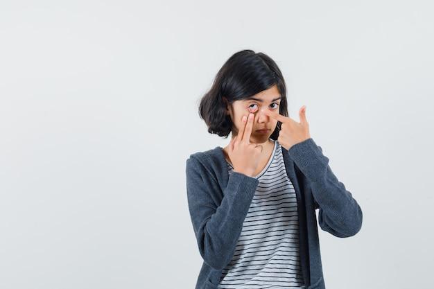 Petite fille pointant sur sa paupière tirée par le doigt en t-shirt, veste