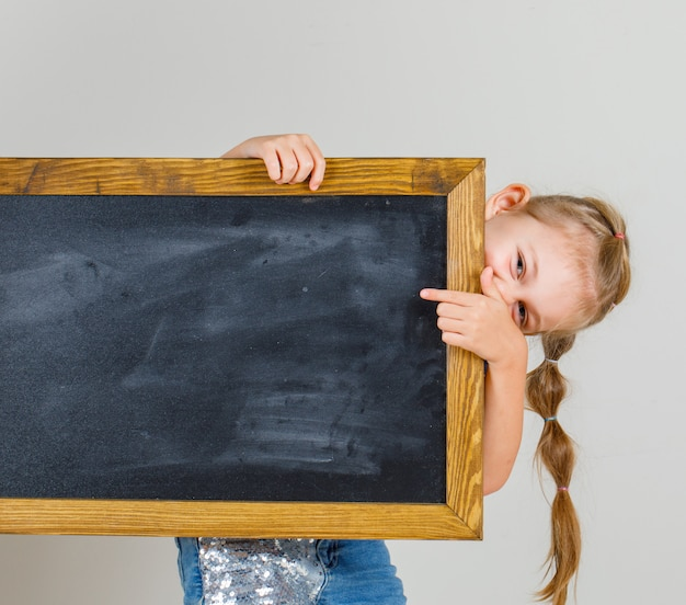 Petite fille pointant sur tableau noir en t-shirt et jupe en jean et à la vue de face, heureux.