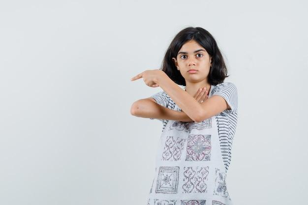 Petite fille pointant vers le côté gauche en t-shirt