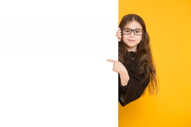 Petite fille pointant vers le fond de la pancarte blanche